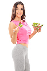 Vertical shot of an attractive woman eating a salad