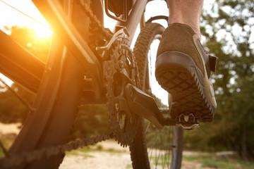 Rear view man peddling bike