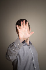 Young Caucasian man hiding his face with hand
