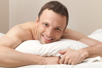 Portrait of pleased Young Caucasian man in bed