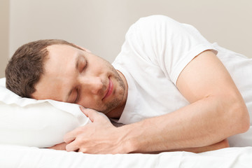 Portrait of pleased sleeping Young Caucasian man in white
