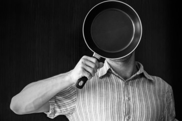 Young man monochrome portrait behind black frying pan