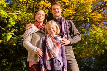 Familie vor bunten Bäumen im Herbst