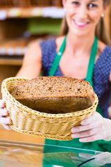 Bäckerei Verkäuferin bietet Kunden Brot an
