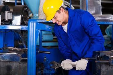 industrial repairman using wrench