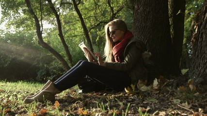 Young woman sitting under the tree with tablet in autumn park