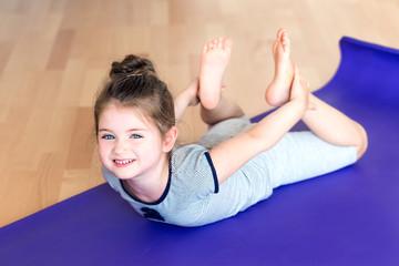 Little girl doiing sports on mat.