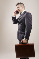 Young businessman with modern hairstyle calling at phone