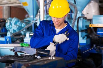 factory mechanic using spanner