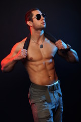 Muscular man in sunglasses poses and holds undershirt the neck
