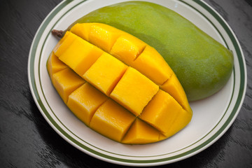 Yellow cubes sliced mango on white plate