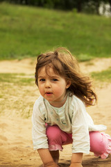 cute kidl is playing and sitting on send in sunny day