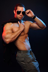 Muscular man in sunglasses posing with jacket over shoulder