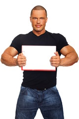 Muscular man in black shirt holds a sign with white paper