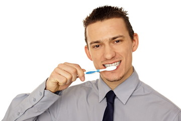 Young businessman cleaning with toothbrush his teeth
