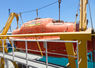 Big red rescue boat hanging on the passenger ship