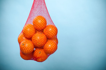 Fresh oranges fruits in mesh from supermarket