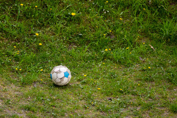 Sport. Old dirty soccer ball on grass. Football.