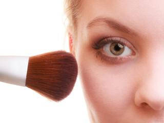 Part of woman face applying rouge blusher makeup detail.