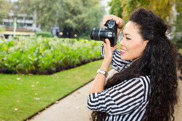 young woman taking photos in the park