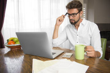 White man holding coffee cup while looking at computer