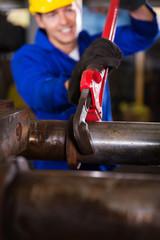 factory mechanic fasten pipe