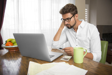 Focused male working at home on his laptop