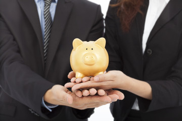 hands of business people holding a piggy bank .financial concept