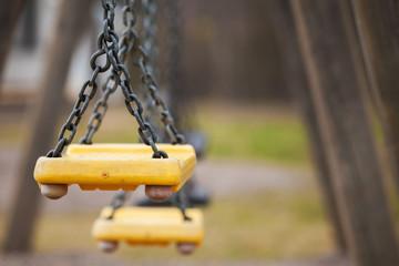 Empty yellow plastic swings on playground