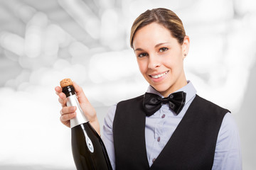 Smiling female waiter holding a champagne bottle