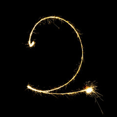 burning sparkler stick and writing sparkling text . number two