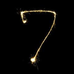 burning sparkler stick and writing sparkling text . number seven