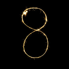 burning sparkler stick and writing sparkling text . number eight