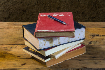 Vintage pencil and old books on wooden deck table with soil wall