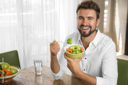 Leinwanddruck Bild Man with perfect skin eating a healthy meal