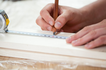 Male hands using measuring tape on wooden board