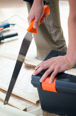 Cutting wooden plank with hand saw