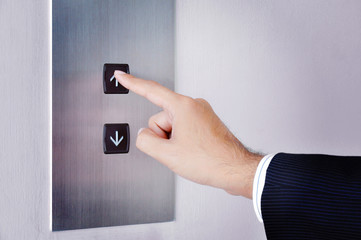 Businessman hand touching going up sign on lift control panel