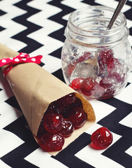 Glace cherries in paper cone on chevron background