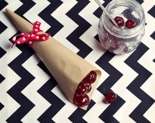 Overhead of glace cherries in a cone and vintage jar