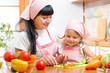 woman and her kid daughter preparing vegetables at kitchen