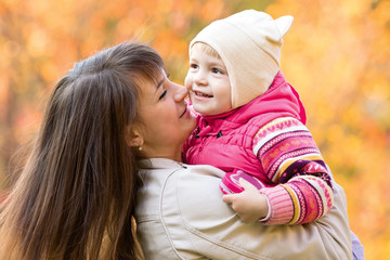 young happy mother with kid girl outdoors in fall