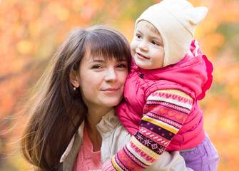 portrait of beautiful mother and child girl outdoors in fall