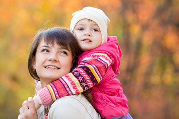happy family - young mother and kid girl together outdoors in fa