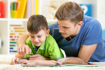 child and his father read a book on floor at home
