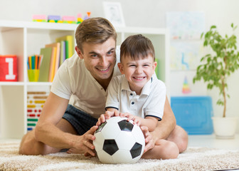 kid boy and father playing with soccerball  indoor