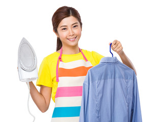 Asian housewife hold iron and shirt