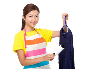 Asian housewife use dust remover on knitwear
