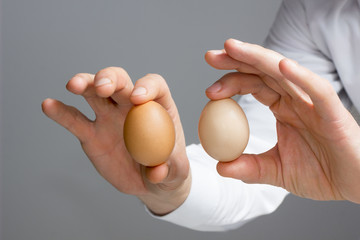 Hands with two hen's eggs.
