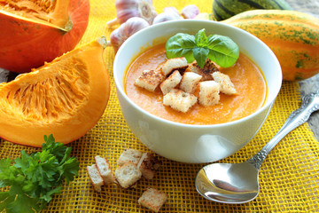 Pumpkin soup in a bowl with fresh herbs and croutons